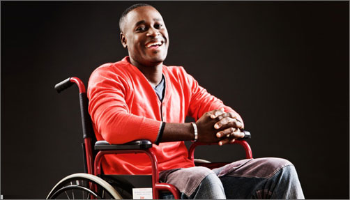 Young man sitting in wheel chair smiling