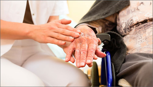 Nurse putting lotion on senior's hand